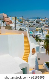 Landscape of city Fira with traditional houses on island of Santorini, Greece. Big yellow staircase in center of white building.