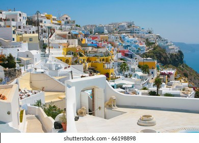 Landscape of city Fira with traditional houses on island of Santorini, Greece. Arch with statue of lions is in front.
