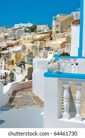 Landscape of city Firostefani with traditional houses on island of Santorini, Greece. Focus on white swan.