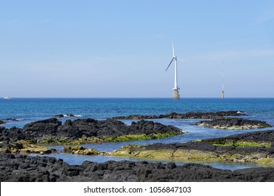 Landscape of coast with wind generator in Gujwa-eup, Jeju, Korea. Jeju Island is famous for beautiful nature and natural World heritage sites.