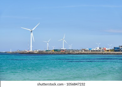 Landscape of coast with wind generator in Woljeong-ri, Jeju, Korea. Jeju Island is famous for beautiful nature and natural World heritage sites.
