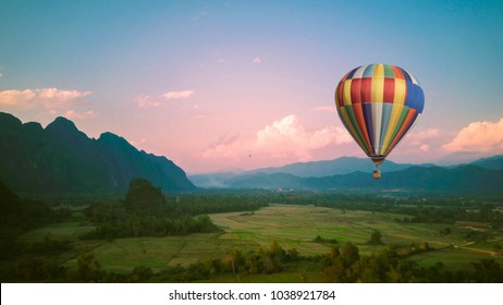 landscape and colorful balloons in countryside with blue sky and clouds