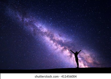 Landscape with colorful purple Milky Way. Night sky with stars and silhouette of a standing sporty girl with raised-up arms on the hill. Beautiful Universe. Space background