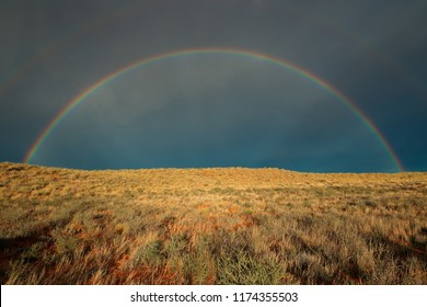 Landscape with a colorful rainbow in stormy sky, Kalahari desert, South Africa