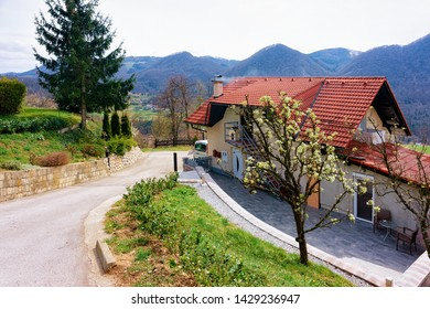 Landscape with cottage house in the countryside of Celje old town in Slovenia. Home architecture at the green hill in Slovenija. Alps mountains on the background.