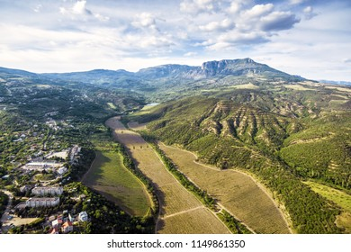 Landscape of Crimea, Russia. Aerial panoramic view of Crimea near Alushta town, Demerdji mountain in the background. Scenery of Southern coast of Crimea in summer. Vineyards in foreground.