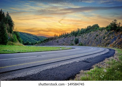 Landscape with curvy road at summer sunset