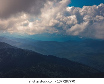 Landscape with dark blue mountains. Evanescent atmosphere in the mountain range wrapped in mist. Mountain forest in clouds landscape. Green mountain range view. Mountain peak blue sky.