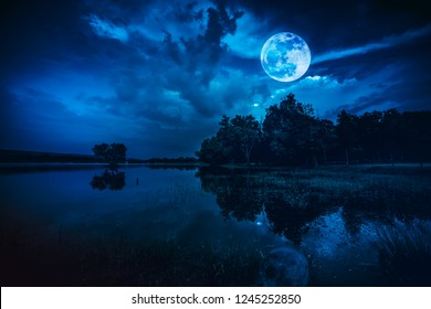Landscape of dark night sky. Beautiful bright full moon and cloudy above silhouettes of trees, river area. Serenity nature background. The moon taken with my camera.