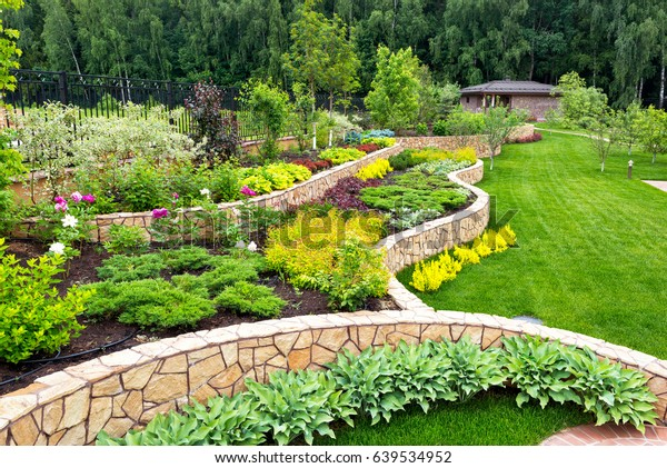 Landscape design with flower beds, natural landscaping panorama in home garden. Beautiful view of nice landscaped garden in residential backyard. Scenery of landscaping area in summer.