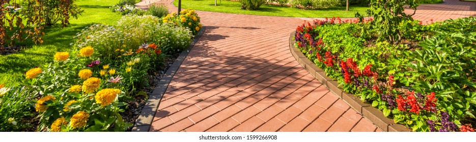 Landscape design in home garden, beautiful lanscaping with flower beds in summer. Panoramic view of landscaped yard or backyard. Scenery of tiled path and green plants at residential house.