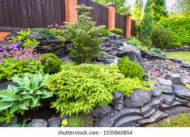 Landscape design in home garden close-up. Detail of beautiful landscaped garden with green plants, rocks and small waterfall. Natural stone landscaping in residential house backyard in summer.