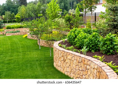 Landscape design in home garden, natural landscaping with plants, trees and decorative stones in residential house backyard. Beautiful landscaped yard with flowerbeds and green lawn in summer.