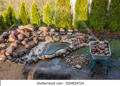Landscape design, the manufacture of alpine slides of granite stone. Laying an artificial reservoir, shrinkage and pouring water. A small artificial pond on an alpine hill. Substitution of soil.