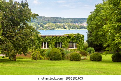 Landscape design with plants and flowers at house in Reichenau Island, Germany. Nice landscaping home garden overlooking Constance Lake (Bodensee). Scenic view of beautiful landscaped backyard.