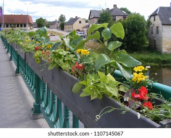 Landscape design in urban environment. Flower boxes near the bridge border. Summertime in the old town streets in city of Dobele - popular tourist destination in Europe, the land of Latvia.