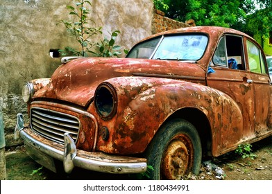 Landscape of an desolated and rusted ambassador that has been sent to the scrapyard