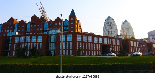 Landscape Dnipro city at sunset. The rays of the setting sun illuminate the red brick buildings on the Dnipropetrovsk Embankment, Ukraine (Dnepr, Dnepropetrovsk)