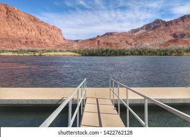 Landscape of a dock or pier, the Colorado River and barren pink hills in the background at Lee's Ferry in Arizona