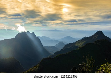 Landscape of Doi Sam Pee Nong before sunset from Doi Luang Chiang Dao's peak, Chiangmai, Thailand. Faraway mountains covered by fog. Sky full of clouds at evening.