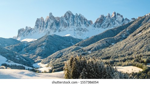 Landscape in Dolomites ski resort in clouds in Tyrol in winter Alps, Italy. Alpine mountains with white snow and blue sky.