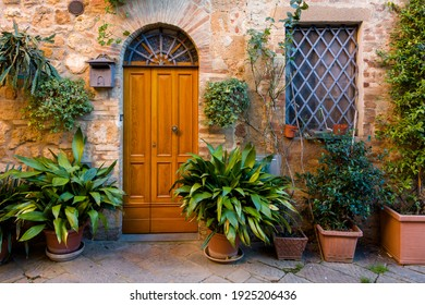landscape with door and plants in pot in old Italian town in Tuscany, Italy in autumn.