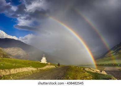 Landscape with double rainbow over the fields with yellow flowers and Buddhist stupa in the rain and clouds in the valley of Zanskar, Himalayas, Northern India.