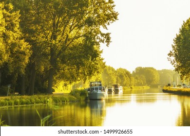 Landscape during sunrise with warm yellow light and moored pleasure boats on a canal named Aarkanaal in Alphen aan den Rijn and banks overgrown with large trees