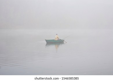 Landscape of an early morning lake and a boat with a fisherman