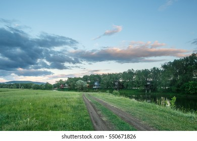 Landscape with eco wooden cottages in oak forest on the river. Beautiful blue sky with big white clouds.