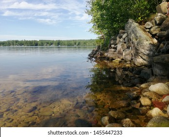 Landscape of the edge of a lake, with a collection of large stones and a tree overlooking the water