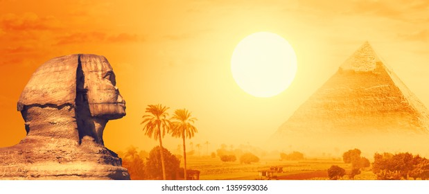 Landscape with Egyptian pyramids, Great Sphinx and silhouettes of palm trees at sunset in Nile valley. Ancient symbols and landmarks of Egypt for your travel concept to Africa in golden sunlight.