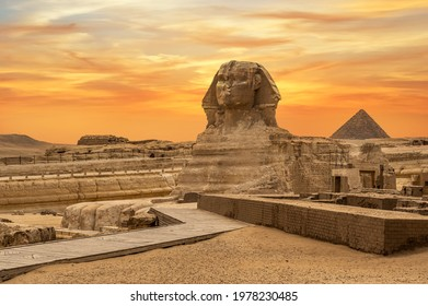 Landscape with Egyptian pyramids, Great Sphinx and silhouettes Ancient symbols and landmarks of Egypt for your travel concept to Africa in golden sunlight. The Sphinx in Giza pyramid complex at sunset