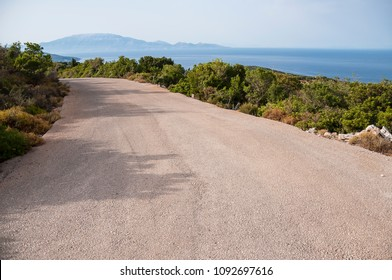 Landscape of empty road during sunny day with mediterranean view on mountains and greek sea. Mountain road during vacation trip with natural environment on roadside.