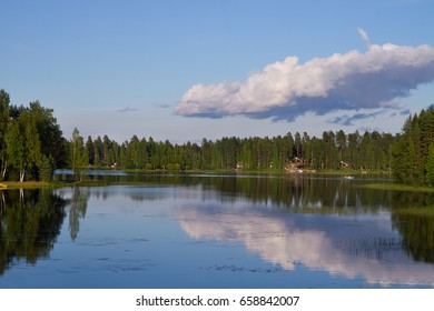 Landscape with finnish lake and forest in a summer day. Skyline and small clouds.