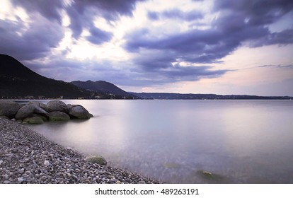 Landscape of Garda Lake, Italy, at sunrise under a cloudy sky in Autumn. Long exposure photography.