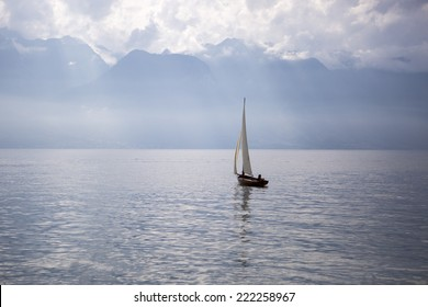 landscape of the Geneva lake with a boat sailing and the Alps mountains in the background - Vevey, Switzerland