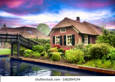 Landscape of Giethoorn village with water canals and rustic houses in netherland. Old small house with thatched roof.