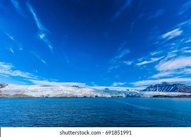 landscape of the glacier Nordensheld in the Arctic Ocean and  with blue sky and mountains with snow on a sunny day, Norway, Spitsbergen, Longyearbyen, Svalbard, summer, winter