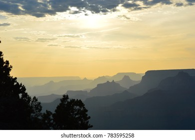 Landscape of the Grand Canyon ridges paled out as the sun peaks from behind a cloud, trees silhouettes in the foreground