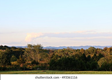 Landscape Of Grassy Field, Trees, Blue Mountains And Sky With Clouds On A Farm In South West Virginia