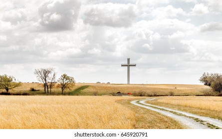 Landscape with a gravel road through a field of dry grass in the foreground leading to a huge cross in the middle of a pasture on the horizon, under cloudy skies. Shot in Adair, Oklahoma.