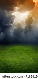 Landscape with green field, dark sky and light from above