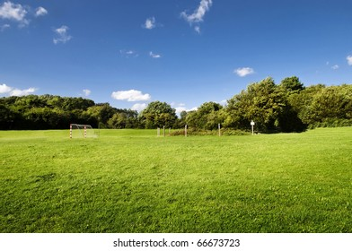 Landscape with green grass, blue sky and soccer goal