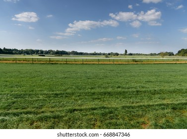 Landscape of green grass hippodrome with blue sky. Turf racecourse in Germany, Magdeburg. Horse track. Green grass field. Background. View from below