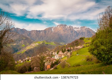 Landscape of green hills in Orobie mountains,background view of mountain peaks in spring time with snow, Seriana valley near Bergamo,Lombardy,italy