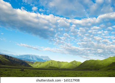 landscape of green meadow, mountain, blue sky and clouds, Russia, Kamchatka