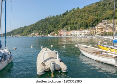 landscape of green shore of Garda lake at touristic village with duck on moored boat, shot in bright fall light at Toscolano-Maderno, Brescia, Italy