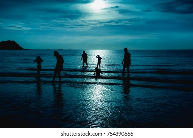 Landscape of green sky with full moon over seascape and silhouette of six person standing in the sea. Family enjoying and relaxing on beach. Serenity nature background. The moon taken with my camera.