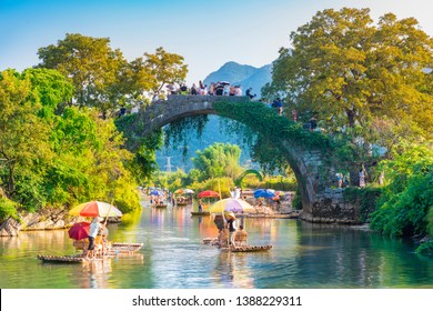 Landscape of Guilin, Yulong River and ancient bridge. Tourists are visiting by Bamboo raft. Located near Yangshuo, Guilin, Guangxi, China.